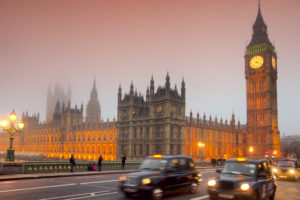 Westminster Palace and Big Ben with london cabs in foreground at dusk
